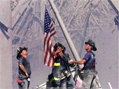 firefighters lifting flag at ground zero