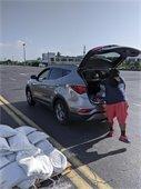 staff putting sandbags in residents car