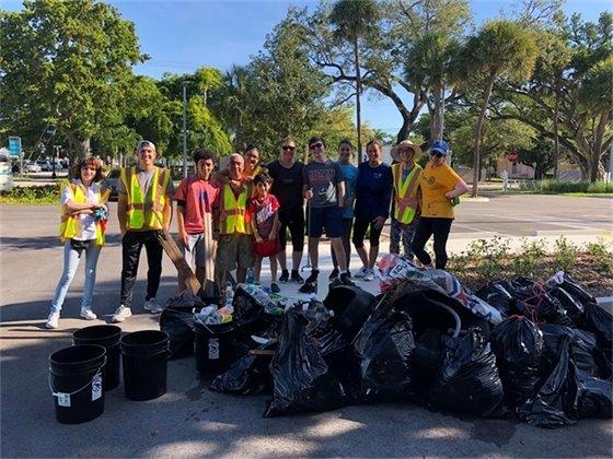 Litter clean up crew behind garbage bags